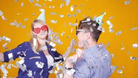 Concept of holiday and birthday. Young happy couple dancing in hats on orange background with confetti stock video footage