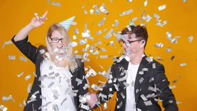 Concept of holiday and birthday. Young happy couple dancing in hats on orange background with confetti stock video