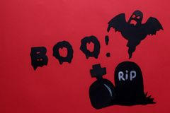 concept of the holiday of Halloween. Cast and grave on a bright red background