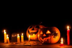 concept of the holiday of Halloween. Halloween pumpkin head with candles inside and around on a wooden table on a black backgroun stock image