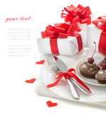 The concept of the holiday menu. For Valentine's Day, birthday sweetheart, March 8, Mother's Day, a plate, spoon, knife, gifts, hearts and cupcakes on a white Stock Photography