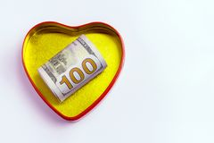 One hundred dollars in a gold heart shaped box with a red outline against a light background. Concept for the holiday St. Valentin. Concept for the holiday St Stock Images