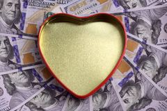 Concept for the holiday St. Valentine`s Day, a gift for the wedding, finance and love. A golden heart box with a red outline agai. A golden heart box with a red royalty free stock photos