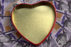 A golden heart box with a red outline against the background of hundred-dollar bills spread out in a circle. Concept for. Concept for the holiday St. Valentine`s Royalty Free Stock Photography