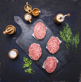 Concept of home cooking chops of marble beeffour cutlets are laid out on vintage cutting board on  blue rustic wooden background Stock Photography