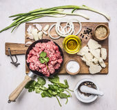 Concept of home cooking minced meat with vegetables, spices and herbs on wooden rustic background top view close up Stock Image