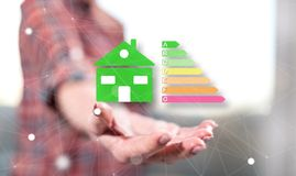 Concept of home energy efficiency. Home energy efficiency concept above the hand of a woman in background royalty free stock image