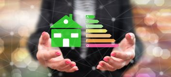 Concept of home energy efficiency. Home energy efficiency concept above the hands of a woman in background royalty free stock photos