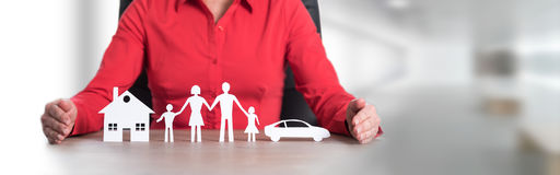 Concept of home, family and car insurance. Insurer protecting house, family and car with her hands Royalty Free Stock Images