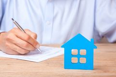 Concept home insurance, rent or purchase. Blue house and Man signs contract in the Stock Photo