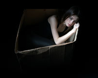 Concept of homeless. Upset girl in cardboard box Stock Images