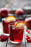 The concept of homemade mulled wine. Sangria or punch with orange, apple and berries in a glass on wooden table. Stock Photo