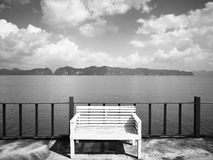 The concept of  hopeless waiting. The white wooden bench is loca. Ted on the balcony.The backdrop of  the foggy island and the sky is full of clouds. Selective Stock Images