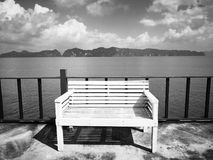The concept of  hopeless waiting. The white wooden bench is loca. Ted on the balcony.The backdrop of  the foggy island and the sky is full of clouds. Selective Stock Image