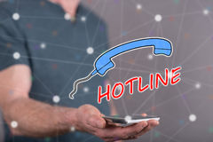 Concept of hotline. Hotline concept above a smartphone held by a man in background Royalty Free Stock Image