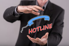 Concept of hotline. Hotline concept between hands of a man in background Royalty Free Stock Image