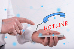 Concept of hotline. Hotline concept above a smartphone held by a man Stock Image