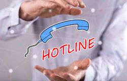 Concept of hotline. Hotline concept between hands of a man in background Royalty Free Stock Images