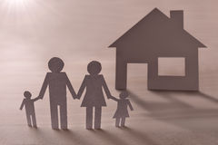 Concept of house and family in paper on wood elevated Royalty Free Stock Photos