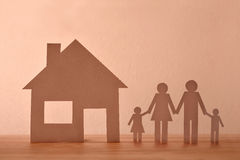 Concept of house and family in paper on wood front Stock Image