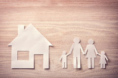 Concept of house and family in paper on wood top Stock Image