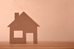 Concept of house in paper on wood front Stock Photos