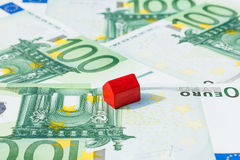 Concept house sell money euro red. Concept house sell, foreclosure, debt, bill, mortgage on 100 euro banknotes. Focus on red house Royalty Free Stock Photo