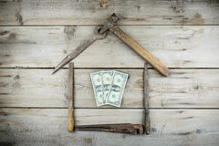 The concept of a house under construction. Old wooden desktop. Old rusty carpentry tools royalty free stock photo