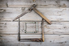 The concept of a house under construction. Old wooden desktop. Old rusty carpentry tools Royalty Free Stock Photos