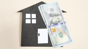 The concept of household, construction and mortgage lending. Dollars fall on a paper bomb. Slow motion stock footage