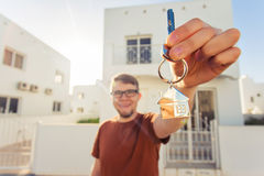 Concept of housewarming, real estate, new home - Young man holding key of new house. Stock Images