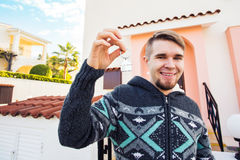 Concept of housewarming, real estate, new home - Young man holding key of new house. Royalty Free Stock Images