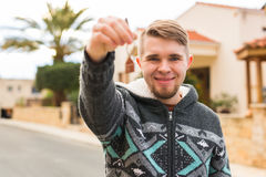 Concept of housewarming, real estate, new home - Young man holding key of new house. Stock Image