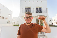 Concept of housewarming, real estate, new home - Young man holding key of new house. Royalty Free Stock Photography