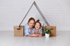 Concept of housing, mortgage and relocation family mother and ch. Ild  with roof and boxes near wall Stock Image