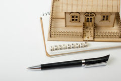 Concept of housing purchase and insurance. Office desk table with supplies top view. Pen, notepad, model house, wooden Royalty Free Stock Photography