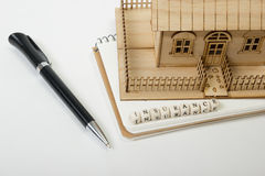 Concept of housing purchase and insurance. Office desk table with supplies top view. Pen, notepad, model house, wooden Stock Photography