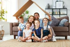 Concept of housing and relocation. happy  big family mother father and kids with roof at home stock photo