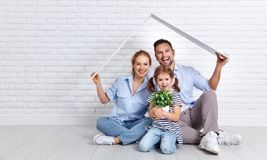 Concept housing young family. Mother father and child in new h. Concept housing a young family. Mother father and child in new house with a roof at empty brick royalty free stock image