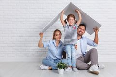 Concept housing young family. Mother father and child in new h. Concept housing a young family. Mother father and child in new house with a roof at empty brick stock images