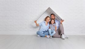Concept housing   young family. Mother father and child in new h. Concept housing a young family. Mother father and child in new house with a roof at empty brick Stock Image