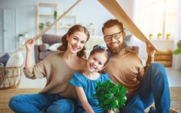 Concept housing   young family. Mother father and child in new house with  roof at home stock photography