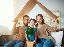 Concept housing   young family. Mother father and child in new house with  roof at home royalty free stock image