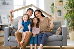 Concept of housing for young family. Mother, father and children girls in the room with a symbol of roof. Concept of housing for young family stock photos