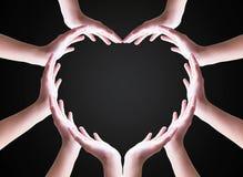 Concept humain international de jour de solidarit? : Mains humaines de collaboration group?es en forme de coeur photos stock