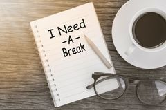 Concept I need a break message on notebook with glasses, pencil. And coffee cup on wooden table royalty free stock images