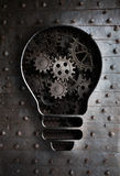 Concept idea: bulb with working gears and cogs Royalty Free Stock Photo