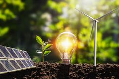 concept idea clean energy in nature. lightbulb with solar panel and wind turbine on soil