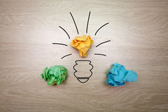 The concept, the idea of colored paper. Crumpled drawn light bulb on wooden background for business presentations Stock Images