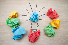The concept, the idea of colored paper. Crumpled drawn light bulb on wooden background for business presentations Royalty Free Stock Images